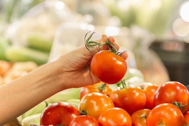 Vrouw die tomaat kiest in groentewinkel
