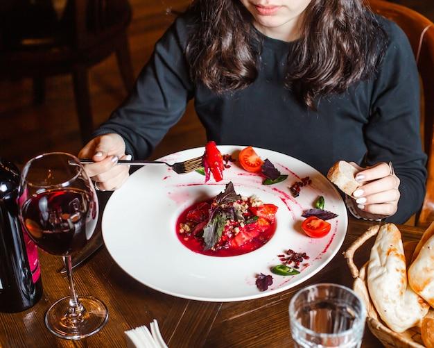Vrouw die tomatensalade in rood sap met okkernoot en kruiden eet