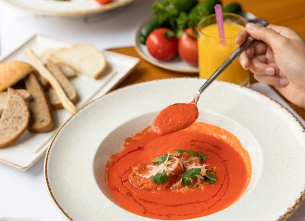 Vrouw die tomatensoep met saus op een witte plaat eet