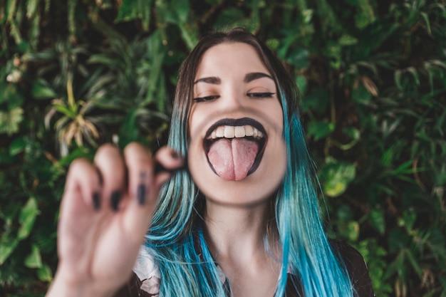 Vrouw die tong toont door een vergrootglas