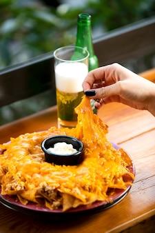 Vrouw die tortillachips mexicaanse chips van plaat neemt,