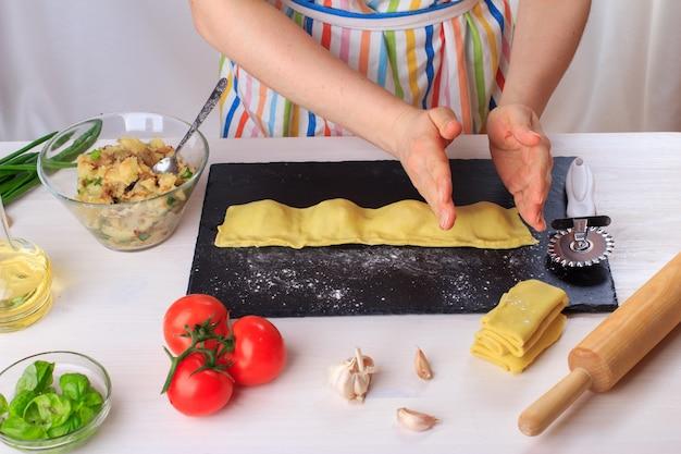 Vrouw die traditionele eigengemaakte italiaanse ravioli kookt