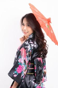 Vrouw die traditionele japanse kimono draagt die op wit wordt geïsoleerd