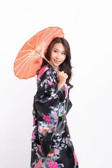 Vrouw die traditionele japanse kimono draagt die op witte achtergrond wordt geïsoleerd