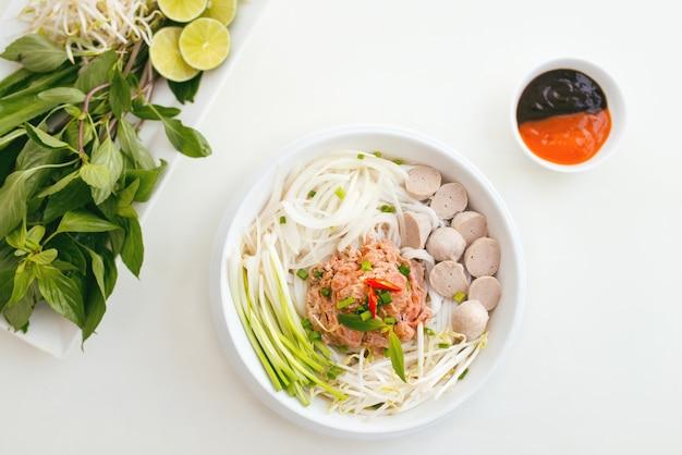 Vrouw die traditionele vietnamese pho-noedels eet met eetstokjes.