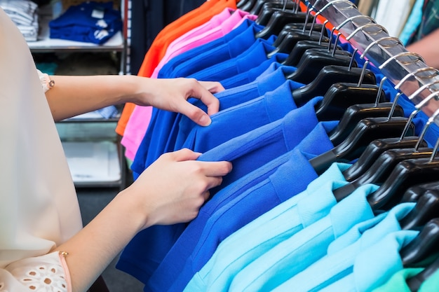 Vrouw die trendy kleurrijk polooverhemd koopt