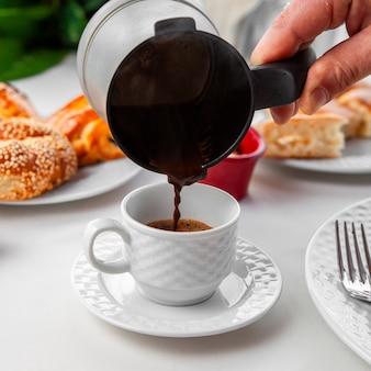 Vrouw die turkse koffie gieten in het zijaanzicht van de koffiekop