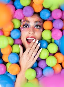 Vrouw die tussen gekleurde ballen ligt, aangenaam verrast met haar hand voor haar mond. gelukkig verrassingsconcept. selectieve aandacht.