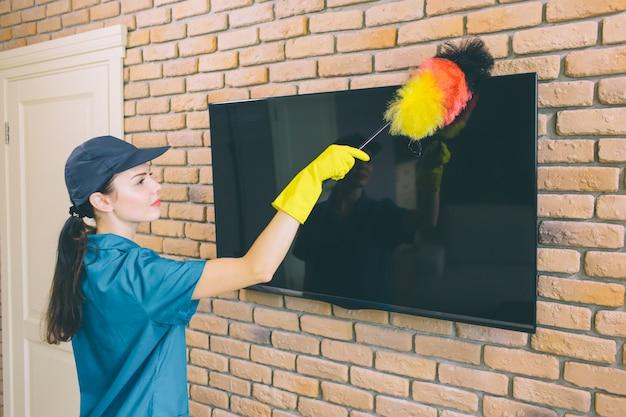 Vrouw die tv schoonmaakt van stof
