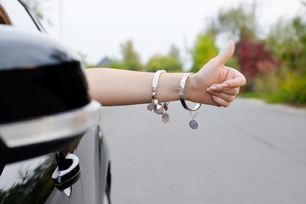 Vrouw die uit auto met juwelen kijkt