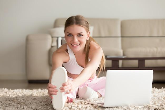 Vrouw die uitrekkende geschiktheidsoefeningen thuis doet