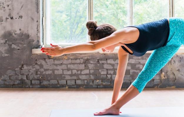 Vrouw die uitrekkende oefening op yogamat doet