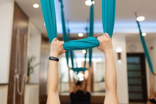 Vrouw die uitrekkende oefeningen van de vliegyoga in gymnastiek doet
