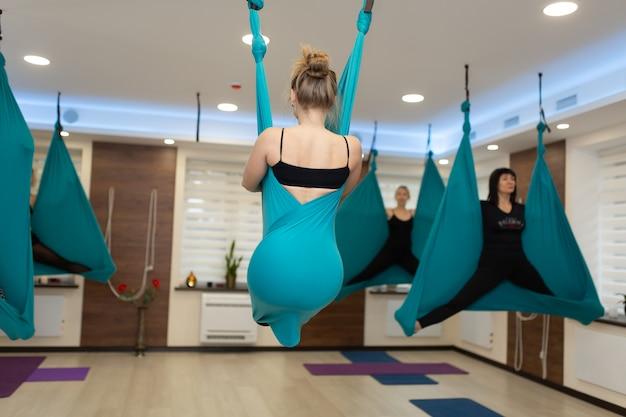 Vrouw die uitrekkende oefeningen van de vliegyoga in hangmat doet. fit en wellness levensstijl.