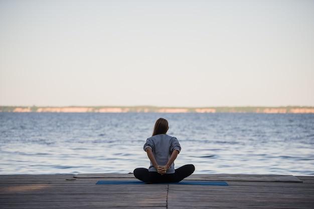 Vrouw die uitrekkende yogaoefeningen in de ochtend doet bij de pijler dichtbij overzees of meer