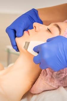 Vrouw die ultrasone gezichtsreiniging ontvangt