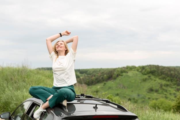 Vrouw die van aard bovenop auto geniet