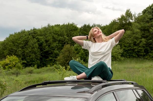 Vrouw die van aard genieten terwijl het stellen bovenop auto