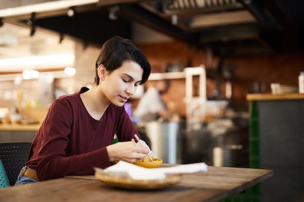 Vrouw die van aziatisch voedsel geniet