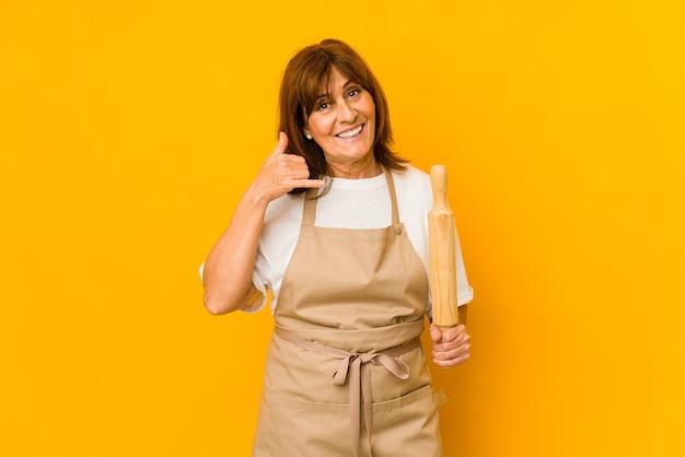 Vrouw die van de middelbare leeftijd de kaukasische kok een geïsoleerde rol houden die een mobiel telefoongesprekgebaar met vingers toont.