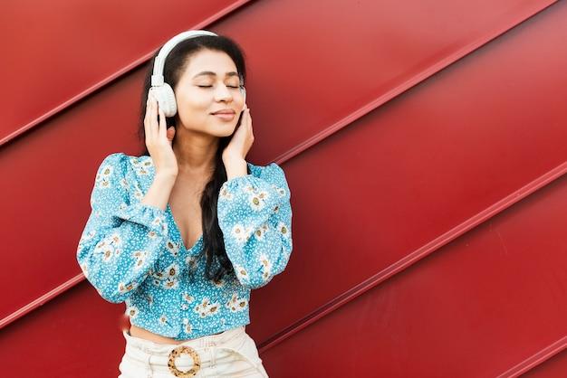 Vrouw die van de muziek op rode tinachtergrond geniet