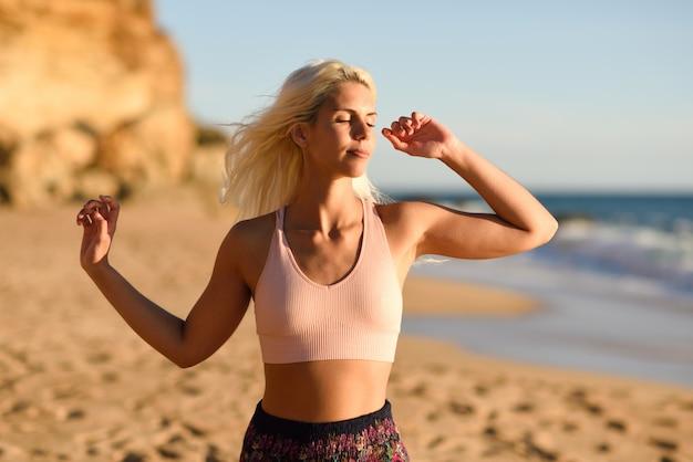 Vrouw die van de zonsondergang op een mooi strand geniet