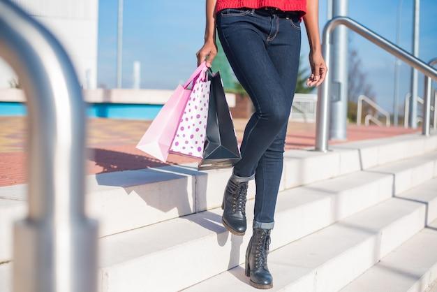 Vrouw die van een winkelcomplex met kleurrijke het winkelen zakken opstapt