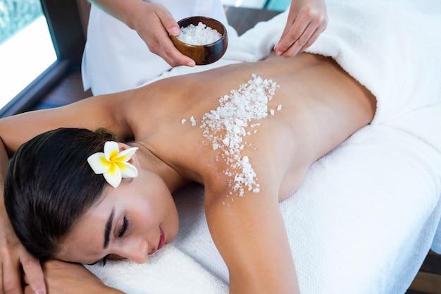 Vrouw die van een zout geniet schrobt massage