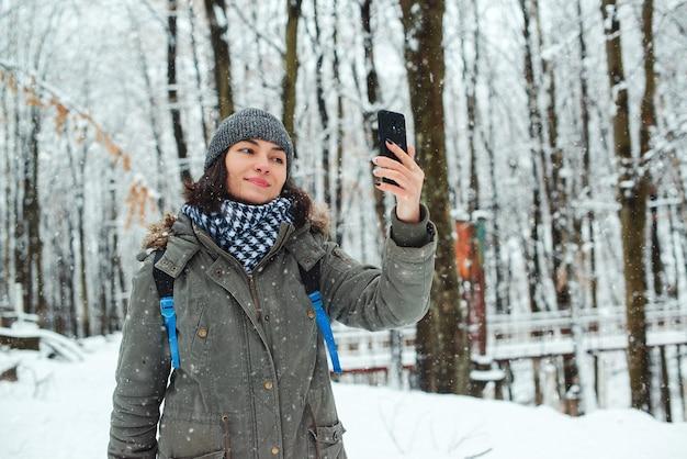 Vrouw die van eerste sneeuw geniet. meisje wandelen in de winter woud. vrouw selfie te nemen door smartphone in de winter.