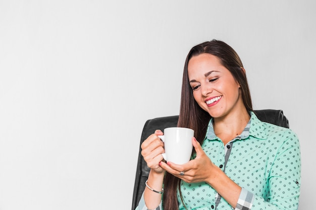 Vrouw die van haar kop van koffie geniet op het kantoor