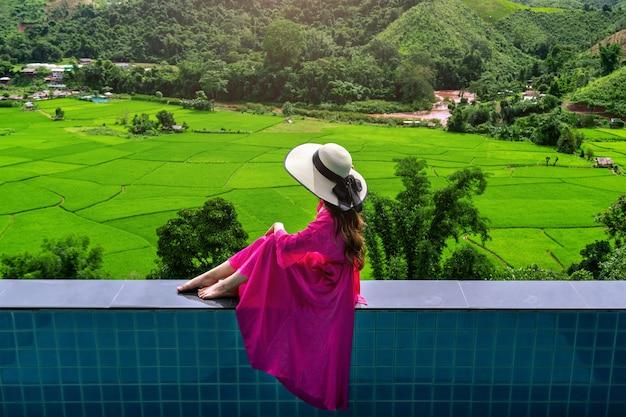 Vrouw die van het gezichtspunt van het rijstterras en groen bos in nan, thailand geniet