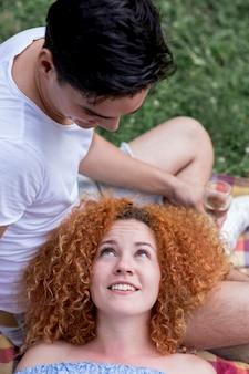 Vrouw die van het hoge hoek de rode haar haar vriend bekijkt
