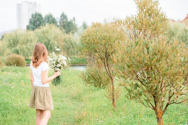Vrouw die van het leven op het gebied met bloemen geniet. aardschoonheid, blauwe bewolkte hemel en kleurrijk gebied met bloemen. outdoor levensstijl. vrijheid concept. vrouw in de zomer veld
