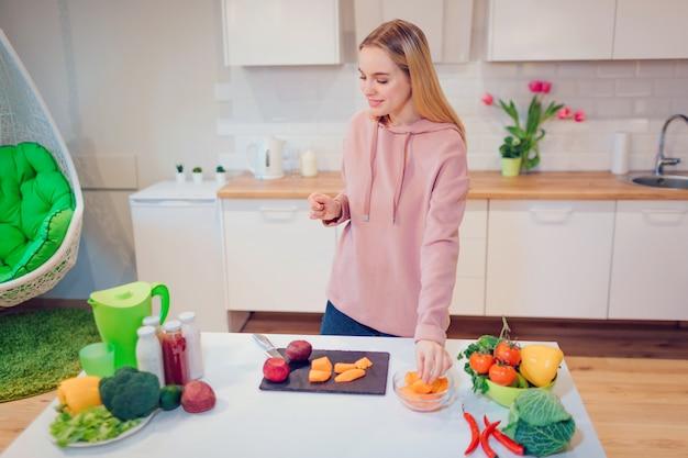 Vrouw die van het veganist de mooie blonde rauwe groenten in de keuken koken.
