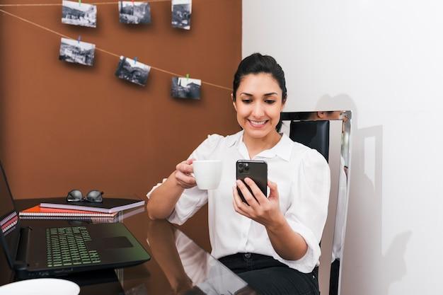 Vrouw die van huis aan koffiepauze werkt terwijl het controleren van haar celtelefoon