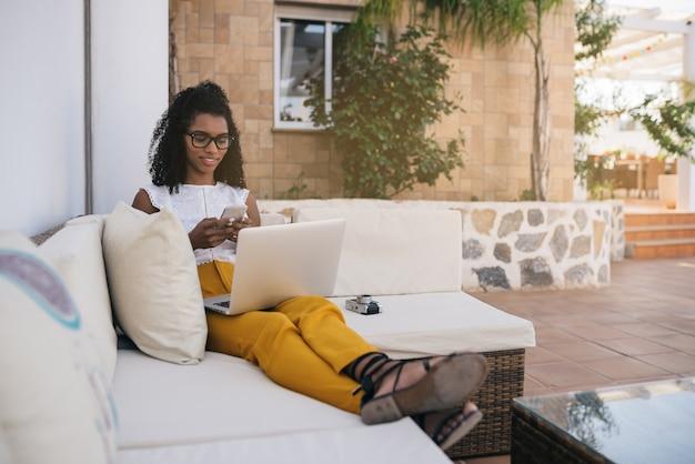 Vrouw die van huis bij de werf aan haar computer werkt