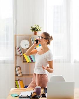 Vrouw die van huis werkt en op telefoon spreekt