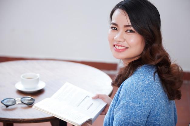 Vrouw die van koffie en boek geniet