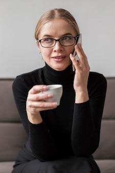 Vrouw die van koffie geniet en over telefoon spreekt