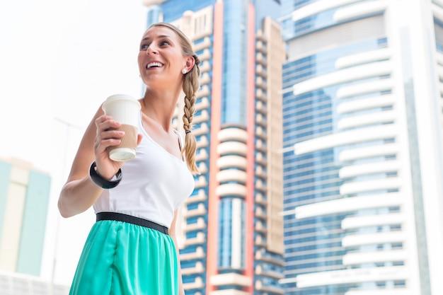 Vrouw die van koffie geniet om in metropolitaanse stad te gaan