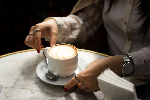Vrouw die van kop van cappuccino geniet