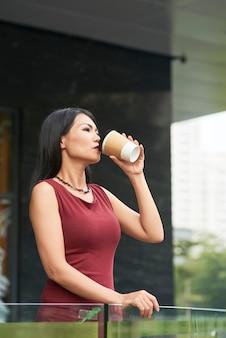 Vrouw die van kop van koffie geniet