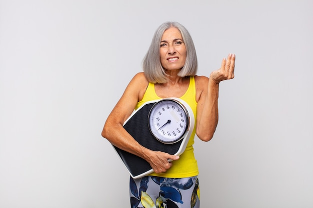 Vrouw die van middelbare leeftijd capice of geïsoleerd geldgebaar maakt