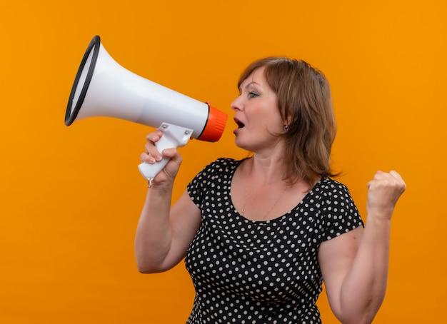 Vrouw die van middelbare leeftijd door spreker spreekt en vuist op geïsoleerde oranje muur opheft