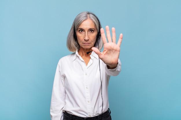 Vrouw die van middelbare leeftijd ernstig, streng, ontevreden en boos kijkt die open palm toont