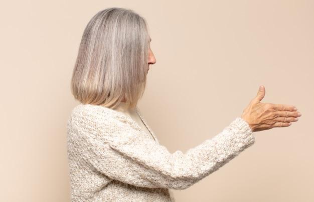Vrouw die van middelbare leeftijd glimlacht, u begroet en een handschud aanbiedt om een succesvolle overeenkomst, samenwerkingsconcept te sluiten