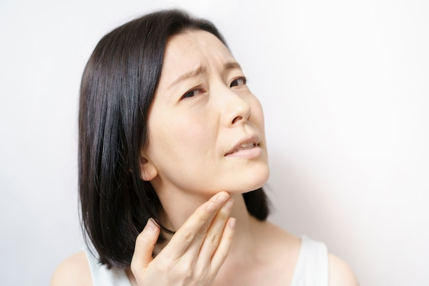 Vrouw die van middelbare leeftijd haar gezicht aanraakt en aan huidproblemen lijdt