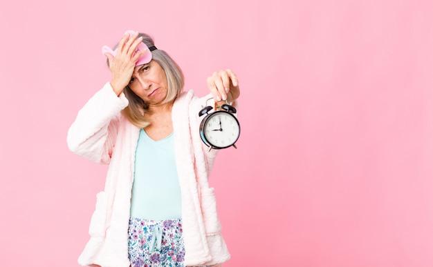 Vrouw die van middelbare leeftijd nachtkostuum met een wekker draagt
