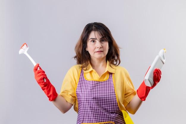 Vrouw die van middelbare leeftijd schort en rubberhandschoenen draagt die schoonmakende levering en schrobborstel houden