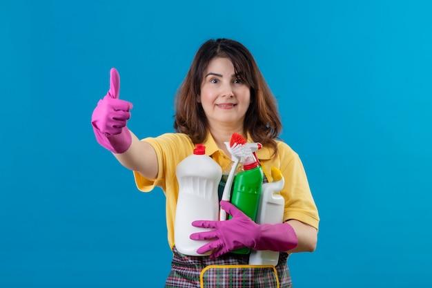 Vrouw die van middelbare leeftijd schort en rubberhandschoenen draagt die schoonmakende levering houden
